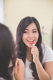 Woman applying red lipstick on her lips, look at the mirror Royalty Free Stock Photography