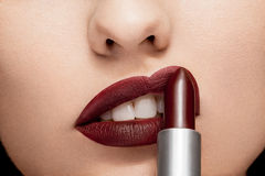 Woman applying red lipstick on lips. In close up photo Royalty Free Stock Photo