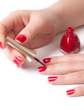 Woman applying red nail polish Stock Images