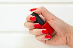 Woman applying red nail polish manicure. Female hand Royalty Free Stock Photography