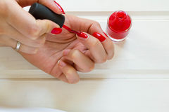 Woman applying red nail polish manicure. Female hand Stock Photography