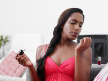 Woman applying red nail varnish on sofa Royalty Free Stock Image