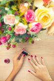 Woman applying red polish on nails. Relax , care and beauty concept stock photo