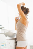 Woman applying roller deodorant on underarm in bathroom Royalty Free Stock Image