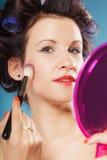 Woman applying rouge blush makeup Stock Photography