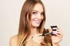 Woman applying rouge with brush to her face Stock Image