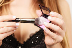Woman applying rouge with brush to her face Royalty Free Stock Photos