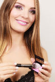 Woman applying rouge with brush to her face Royalty Free Stock Image