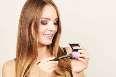 Woman applying rouge with brush to her face Stock Photography