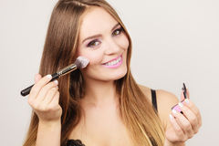 Woman applying rouge with brush to her face Stock Photos