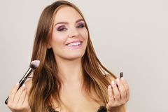 Woman applying rouge with brush to her face Royalty Free Stock Images