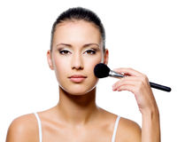Woman applying rough on beautiful face Royalty Free Stock Images