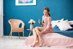 Woman applying skin lotion indoors. Young woman applying a lotion on her legs sitting on the bed in the beautiful pink and blue bedroom interior Stock Photos