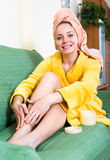Woman applying skin lotion to legs royalty free stock image