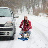 Woman applying Snow Chains Stock Photography