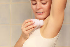 Woman applying stick deodorant in armpit Royalty Free Stock Photography