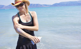 Woman applying sun block lotion while at the beach Stock Images