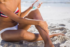 Woman applying sun cream on her leg Stock Photography