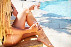 Woman applying sun cream. Sexy blond woman in bikini relaxing be Royalty Free Stock Photos