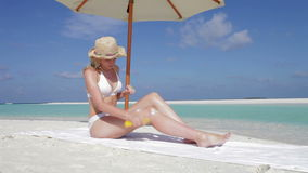 Woman Applying Sun Lotion On Beach Holiday. Woman applies sun lotion spray before lying on beach towel.Shot on Canon 5d Mk2 with a frame rate of 30fps stock footage