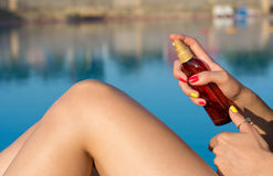 Woman applying sun lotion by the pool Royalty Free Stock Images