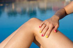 Woman applying sun lotion by the pool Royalty Free Stock Image