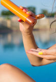 Woman applying sun lotion by the pool Royalty Free Stock Photos