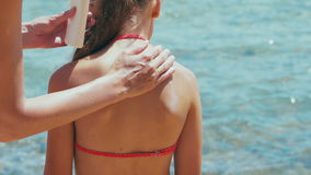 Woman applying sun protection cream lotion on her daughter`s shoulder stock footage