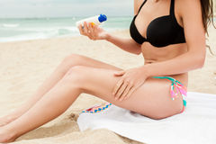 Woman applying sun protection lotion. Royalty Free Stock Images