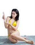 Woman applying sunblock. Beautiful young woman applying sunblock sitting on the mat Stock Photos