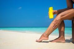 Woman applying sunblock cream on leg on beautiful tropical beach Royalty Free Stock Image