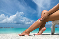 Woman applying sunblock cream on leg on beautiful tropical beach Royalty Free Stock Photography