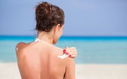 Woman is applying sunblock Stock Image