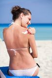 Woman is applying sunblock Royalty Free Stock Image
