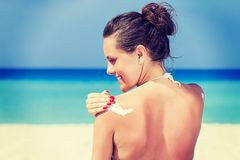 A woman is applying sunblock. A smiling woman is applying sunblock on the beach Royalty Free Stock Images