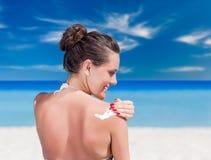 A woman is applying sunblock Stock Photos