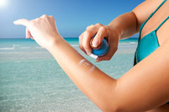 Woman applying sunscreen Royalty Free Stock Images