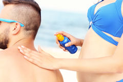 Woman applying sunscreen on the back of her man Royalty Free Stock Image