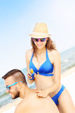 Woman applying sunscreen on the back of her man Stock Image