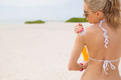 Woman applying sunscreen on the beach stock images