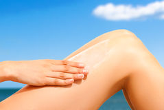 Woman applying sunscreen at the beach Royalty Free Stock Images