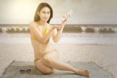 Woman applying sunscreen at coast Stock Photo