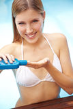 Woman applying sunscreen on hand. Attractive smiling blond woman applying sunscreen on her hand Royalty Free Stock Images