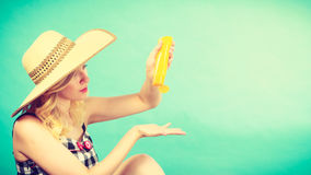 Woman applying sunscreen on hand. Sunburns, safe sunbatching, tannig during summer concept. Woman wearing sun hat applying sunscreen on hand. Studio shot on blue Royalty Free Stock Photo