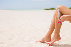 Woman applying sunscreen on her legs Royalty Free Stock Photos