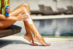 Woman applying sunscreen on her smooth tanned legs Royalty Free Stock Photography