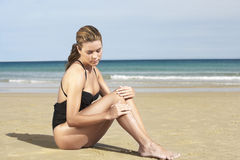 Woman Applying Sunscreen On Legs At Beach Stock Photography