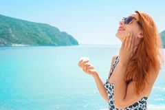 Young woman applying sunscreen sunblock lotion by seaside smiling happy outdoors stock photography