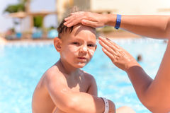 Woman applying sunscreen to the face of her son Stock Photos