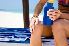 Woman applying suntan lotion Stock Photo